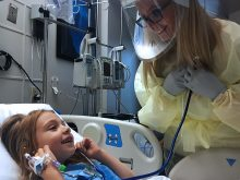 Kendalyn lies back and listens for Chelsie's heartbeat through a stethoscope.